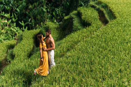 A man and a woman among the rice terraces. A couple in love is traveling in Asia. A man and a woman are traveling in Indonesia. Happy couple in Bali. Rice terraces in Bali. Copy space