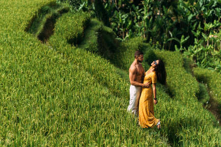 A man and a woman among the rice terraces. A couple in love travels through Asia. Man and woman are traveling in Bali. Happy couple in Bali. The couple travels the world. Rice terraces in Bali.