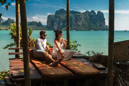 Beautiful couple relaxing on an island off the coast. Young couple by the sea. A man and a woman travel to Thailand. Couple in love at the lagoon. Honeymoon trip. Relax on the island. Wedding travel 版權商用圖片