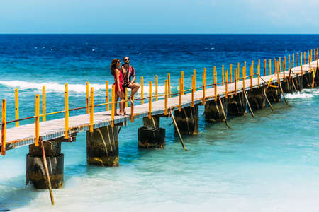 A beautiful couple on vacation strolling along a wooden pier above the tropical, turquoise ocean in Nusa Penida, Indonesia. Couple on vacation. Lovers on the coast. Lovers walk along the pier