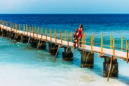A beautiful couple on vacation strolling along a wooden pier above the tropical, turquoise ocean in Nusa Penida, Indonesia. Couple in romantic walk along tropical ocean pier. Couple walks on pier