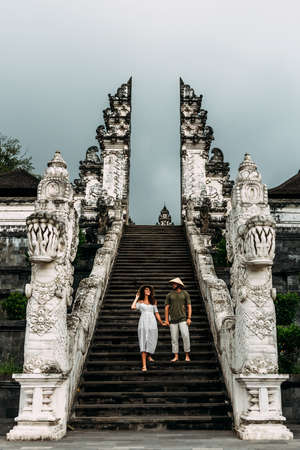 A couple stands on the stairs of the Baltic temple. Man and woman traveling in Indonesia. Couple at the Bali gate. The couple travels the world. Tourists in Bali. Copy space. Vertical photo