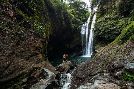 A man holds a woman in his arms at the waterfall. Couple at the waterfall, rear view. Honeymoon trip. Happy couple on vacation in Bali. A couple in love travels the world. Copy space