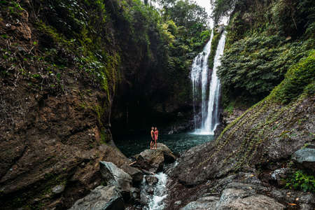 A man holds the hand of a beautiful woman at a waterfall. A couple in love on a waterfall. Honeymoon trip. Happy couple on the island of Bali. Beautiful couple travels the world. Travel to Indonesia 版權商用圖片