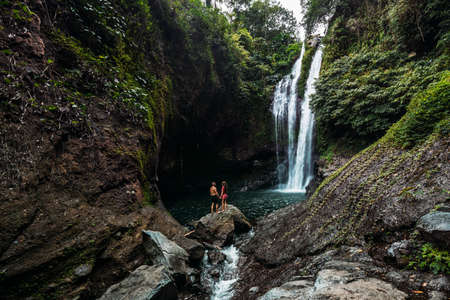 A couple in love on a waterfall. Honeymoon trip. Happy couple on the island of Bali. Beautiful couple travels the world. Travel to Indonesia. Happy couple on vacation. Wedding trip. Copy space 版權商用圖片