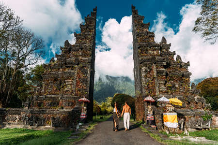 Happy couple having fun in Asia. Couple at the Bali gate. A man and a woman traveling on the island of Bali Indonesia. The couple travels the world. Man and woman in a Balinese temple at sunset