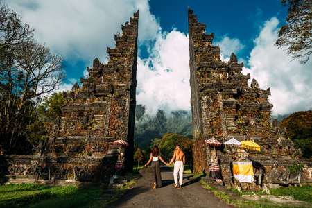 Beautiful couple at the Bali temple. Man and woman traveling in Indonesia. Couple at the Bali gate. The couple travels the world. Travel to tourist places in Asia. Tourists in Bali. Copy space.