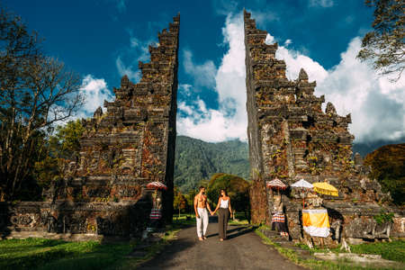 Traveling couple in Bali. Happy couple vacationing in Asian countries. Couple at the Bali gate. A man and a woman traveling on the island of Bali Indonesia. The couple is traveling in Indonesia