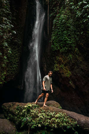 A man at the waterfall. A person travels around the world. The man at the waterfall. Travel to Bali, Indonesia. A person travels through picturesque places. A lone traveler. Copy space
