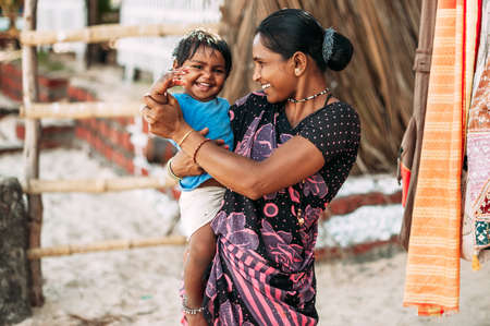 India, Goa, the village of Benaulim - November 15, 2012: Unidentified Indian woman and baby in her arms are smiling with very good mood. A mother and her child 新聞圖片