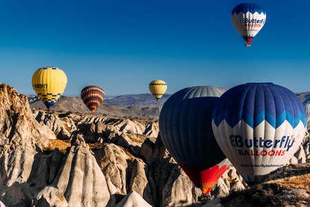 Balloons in the sky over Turkey at sunrise. Colorful balloons move in the blue sky over Goreme. Cappadocia Balloon Festival. Hot air balloons flight in Turkey. Festival of balloons.