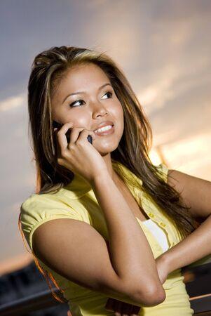 filipino ethnicity: talking on mobile phone outside enjoying sunset Stock Photo