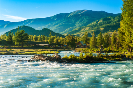 residential idyll: Blue wide river flowing in front of the house in the mountains Stock Photo