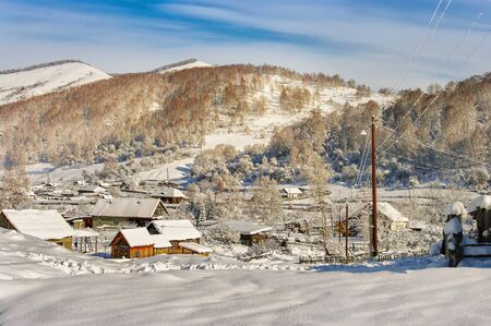 log cabin in snow: View of the village in the mountains on a sunny day in winter