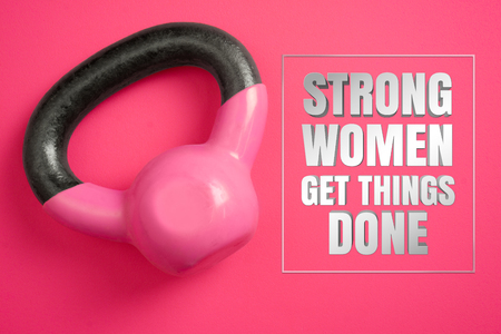 Strong women get things done. Inspirational quote with womens kettle weights on pink background. Stock Photo