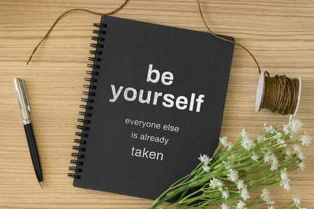 Notebook with motivational and inspirational wisdom quote on wood desk. Be yourself, everyone else is already taken.