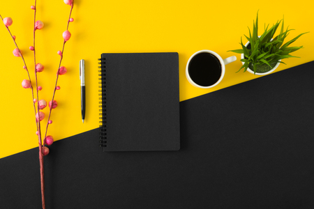 Black sketch pad with coffee cup on yellow and black background. Banco de Imagens
