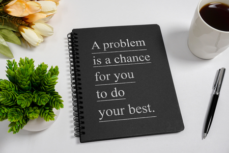 Notebook with wisdom quote and coffee cup on white background. Stock Photo