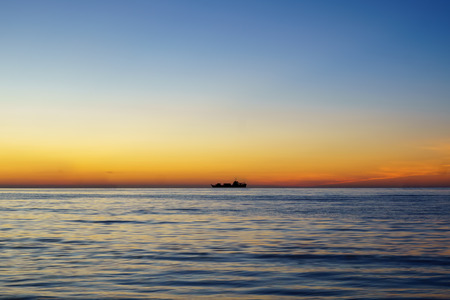 Silhouette of sailing ship far away at the sea horizon during sunset. With text copy space.