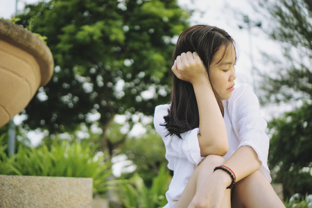 Sad young Asian woman sitting in a park.