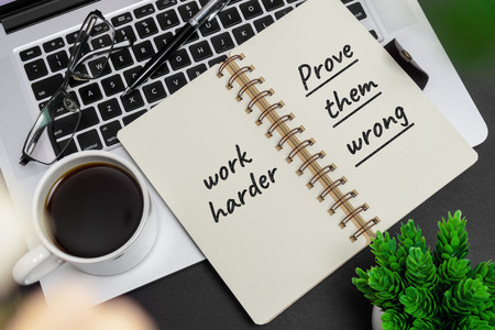 Inspirational and motivation life and business quote on notepad with laptop - Work Hard. Prove Them Wrong.
