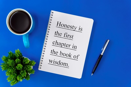 Notebook, pen and coffee mug on blue background. Inspirational life quote on notepad.