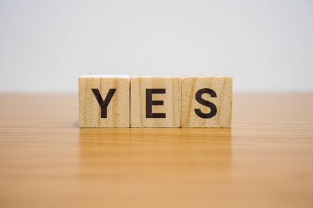 Wooden block on desk with the word Yes.