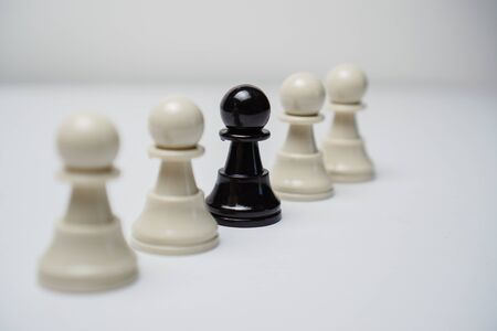 One black pawn among white pawns in a line. Chess concept.
