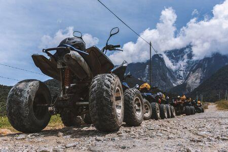ATV (All-terrain Vehicle) parked on dirt gravel road with view of Mount Kinabalu at Kundasang Sabah.