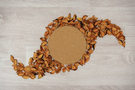 Overhead view of cork board with copy space and dry flower petals on table. Stock fotó