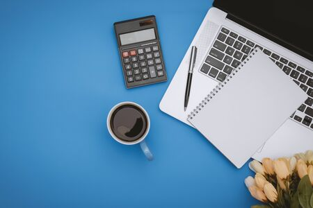 Overhead View of Laptop, Notebook and Calculator over Pastel Blue Background
