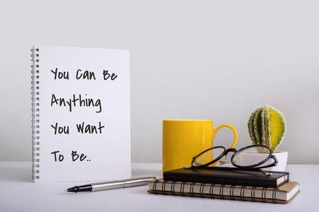 Cahier à spirale avec citation de sagesse inspirante et motivante sur un bureau blanc.