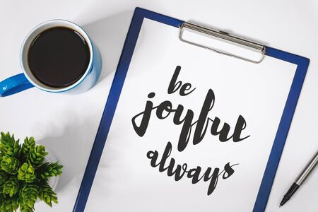 Motivational and Inspirational Quotes. Be Joyful Always. Still Life of Clipboard on Work Desk.