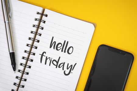 Overhead View of Hello Friday on Notebook over Work Desk. Banco de Imagens