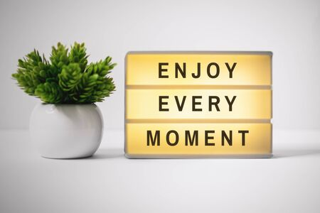 Motivational and Inspirational Quotes. Enjoy Every Moment. Still Life of Lightbox on Work Desk. Banco de Imagens