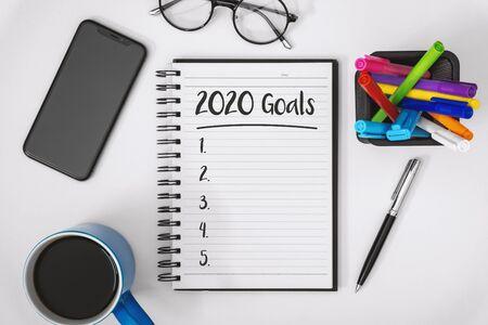 Overhead view of 2020 Goals List on Notebook over Work Desk. Banco de Imagens