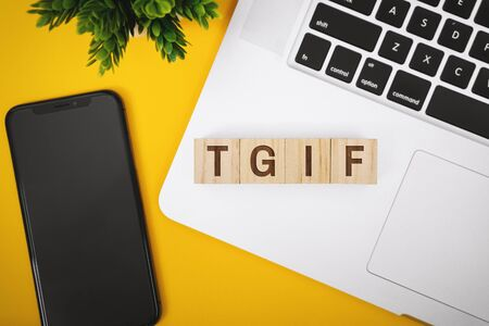 TGIF Text on Word Block on Laptop over Work Desk. Banco de Imagens