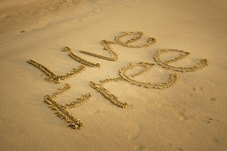 Live Free Written on Beach Sand. Freedom and Life Exploration Concept. Banco de Imagens