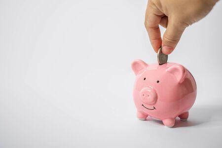 Close Up of Hand Putting Coin Into Piggy Bank. Saving Money Concept. Banco de Imagens
