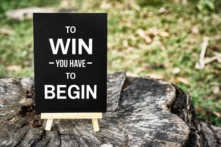 Inspirational and Motivational Quote. To Win You Have To Begin. Mini Blackboard on Wood. Banco de Imagens