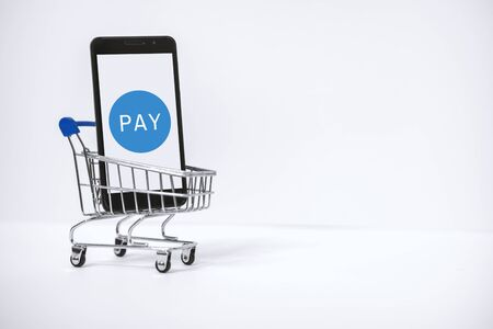 Mobile E-Payment. Mobile Phone Inside Shopping Cart. Cashless Payment Concept. Banco de Imagens