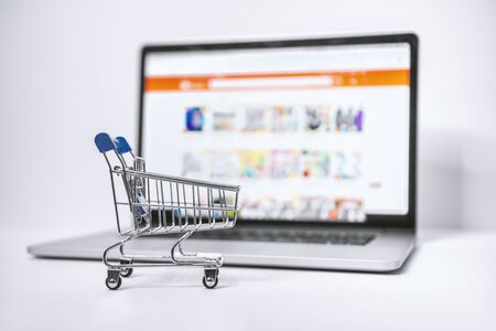 E-Shopping Concept. Shopping Cart and Laptop. Shopping Cart on Blue Background.
