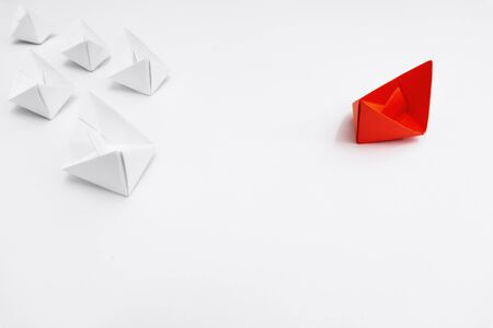 A Different Approach. Red Paper Boat Taking Different Route From The Rest. Banco de Imagens