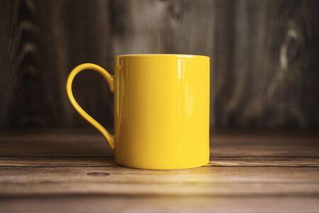 Close Up Shot of Yellow Coffee Mug on Wooden Desk Banco de Imagens