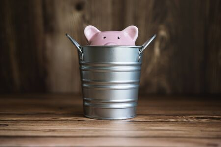Piggy Bank Sinking Inside Steel Bucket. Business and Financial Recession Concept.