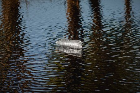 Plastic Bottle in the River. Environmental and Pollution Concept.