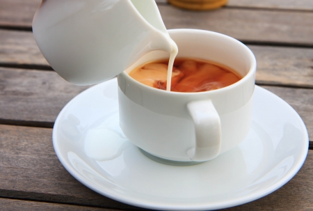 Pouring milk from jar into a cup of tea or coffee