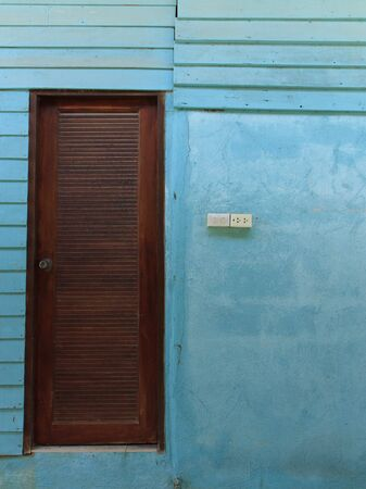 wood door and blue wall Stock Photo