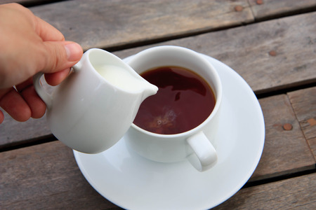 Pouring milk from jar into a cup of tea or coffee photo