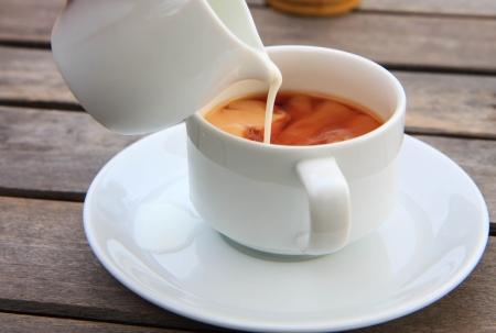 Gießen Milch aus Glas in einer Tasse Tee oder Kaffee Standard-Bild